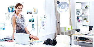 Young woman photographer processing pictures sitting on the desk Royalty Free Stock Photos
