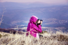 Young woman photographer sitting in the mountain taking pictures Royalty Free Stock Photography