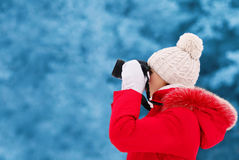 Young woman photographer takes picture on the digital camera outdoors in winter Royalty Free Stock Images
