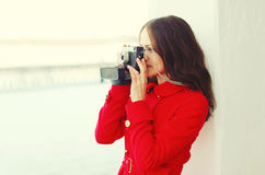 Young woman photographer takes picture on vintage camera in winter city Royalty Free Stock Photo