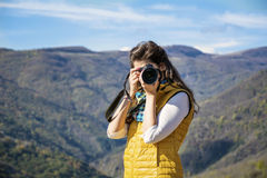 Young woman photographer taking photo of a beautiful mountain Royalty Free Stock Image