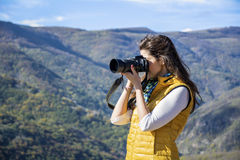 Young woman photographer taking photo of a beautiful mountain. Brunette woman photographer in a beautiful mountain Stock Images