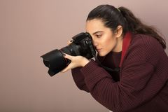Young woman photographer taking a photo. With a professional DSLR and lens bending forwards as she focuses on her subject in a side view stock photo