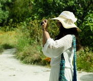 Young woman photographer taking photo, summer day Royalty Free Stock Photography