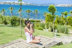 Young woman photographer taking photos in a green tropical garden with sea view Stock Photos