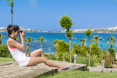 Young woman photographer taking photos in a green tropical garden with sea view Stock Images