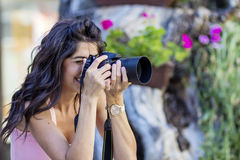 Young woman photographer taking photos outdoor Stock Image