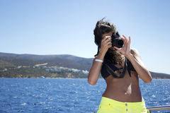 Young woman photographer taking photos on a sea background Royalty Free Stock Image