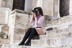 Young woman photographer taking photos sitting on a stone stairs Royalty Free Stock Images
