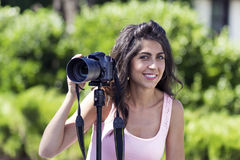 Young woman photographer taking photos with tripod outdoor Stock Photo