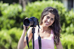 Young woman photographer taking photos with tripod outdoor Royalty Free Stock Photography