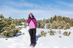 Young woman photographer taking photos in the winter mountain Royalty Free Stock Photos
