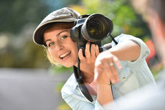 Young woman photographer taking shots Royalty Free Stock Image
