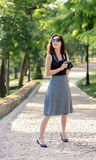 Young woman photographer, tourist in a blue skirt and black to royalty free stock photography