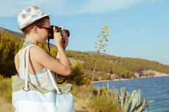 Young woman photographer, tourist using digital camera taking photo by the sea Stock Photography