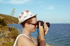 Young woman photographer, tourist using digital camera taking photo by the sea Royalty Free Stock Images