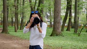 Young woman photographer working process shooting outdoors in park nature stock video footage
