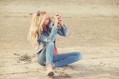 Young woman photographing on the beach Stock Photos