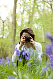 A young woman photographing bluebells, smiling Royalty Free Stock Images