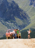 Young woman photographing four friends standing beside parked jeep on dirt track in mountain valley Stock Image