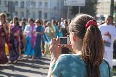 Young woman photographing a group of hare Krishna. Young woman photographing group of hare Krishna Royalty Free Stock Image