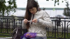 Young woman photographing her lunch in the park in a cloudy day stock footage