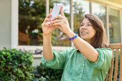 Young woman photographing herself in a cafe Royalty Free Stock Photos