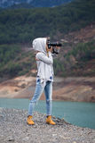 Full length portrait of young woman photographing landscape. Using long range lens and dressed in grey hood jeans and boots of ocher color with river and Royalty Free Stock Photos