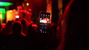 Young woman photographing music concert, standing outdoors in summer outdoor festival night party concert. Female fan. Takes photo of holiday event, using stock video footage