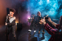 Young woman photographing rock and roll band performing hard rock music Royalty Free Stock Photo