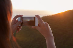 Young woman photographing sunset with Smart phone camera Stock Image