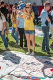Young Woman Photographs AIDS Quilt Section Stock Photo