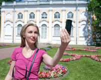 Young woman photographs herself on the cell phone against pavilion Stone  hall in Oranienbaum, Petersburg, Russia Royalty Free Stock Photos