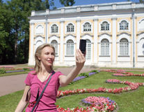 Young woman photographs herself on the cell phone against pavilion Stone  hall in Oranienbaum, Petersburg, Russia. Royalty Free Stock Photos