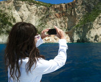 Young woman photographs the island in Greece Stock Photo