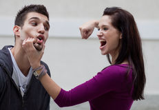 Young woman physically abusing her boyfriend Royalty Free Stock Photography