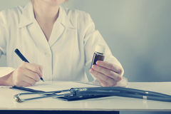 Young woman physician with stethoscope prescribing Stock Photo