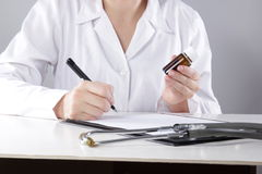Young woman physician with stethoscope prescribing Royalty Free Stock Images