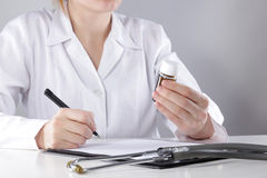 Young woman physician with stethoscope prescribing treatment to patient. Female doctor  writing recipe on clipboard in Royalty Free Stock Photo