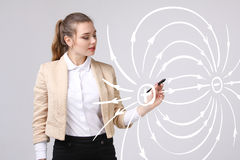 Young woman, physics teacher draws a diagram of the electric field Royalty Free Stock Photos