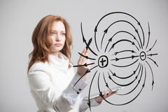 Young woman, physics teacher draws a diagram of the electric field Royalty Free Stock Photo