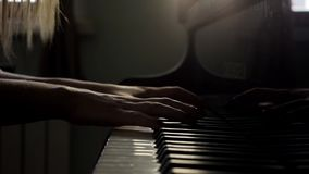 Woman hands finish playing classical music on the piano close-up in slow motion. Young woman pianist two hands finish playing gentle classical music on a stock video
