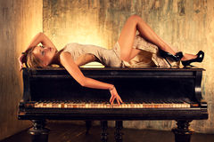 Young woman on piano. Young elegant woman in dress lying on piano in retro style interior royalty free stock images