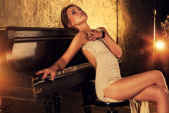 Young woman at piano. Young elegant woman in dress sitting at piano in retro style interior Stock Image