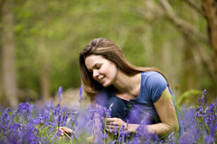 A young woman picking bluebells, smiling Royalty Free Stock Photo
