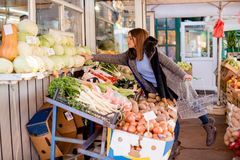 Young woman picking cabbage at farmer`s market Royalty Free Stock Photography