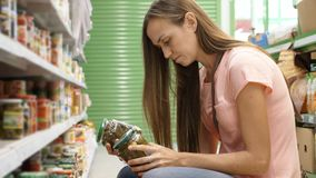 Woman picking canned food from the shelves at supermarket and reading the label Stock Photo