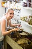 Young woman picking dried beans in store Royalty Free Stock Photo
