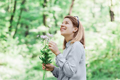 Young woman picking flowers in nature. Young woman picking flowers outside in nature Royalty Free Stock Photo