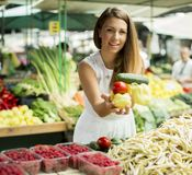 Young woman picking fresh vegetable at market